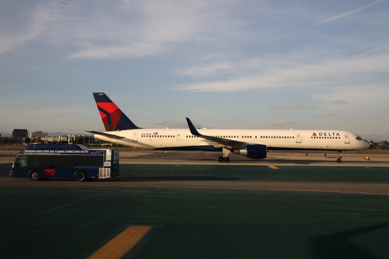 FILE PHOTO:  A Delta plane passes a Delta bus on the tarmac at LAX airport in Los Angeles