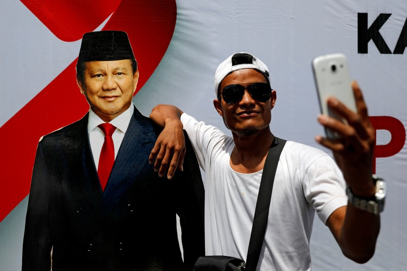 FILE PHOTO: Man takes selfie pictures with a cutout of Indonesia's presidential candidate for the upcoming election Prabowo Subianto during a campaign rally in Solo