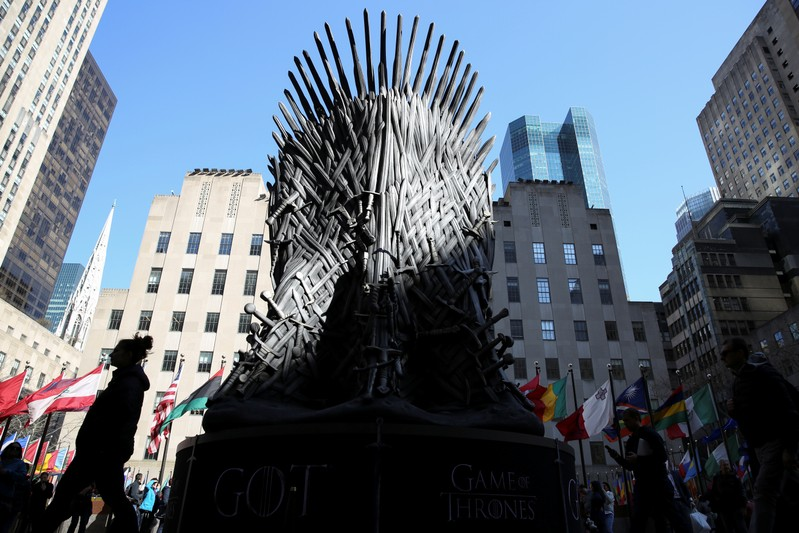 People walk past a large replica of the iron throne before the premiere of the final season of