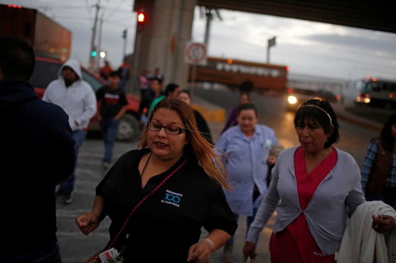 FILE PHOTO: Workers of assembly factories cross a street as they rush toward their shift at an industrial park in Reynosa