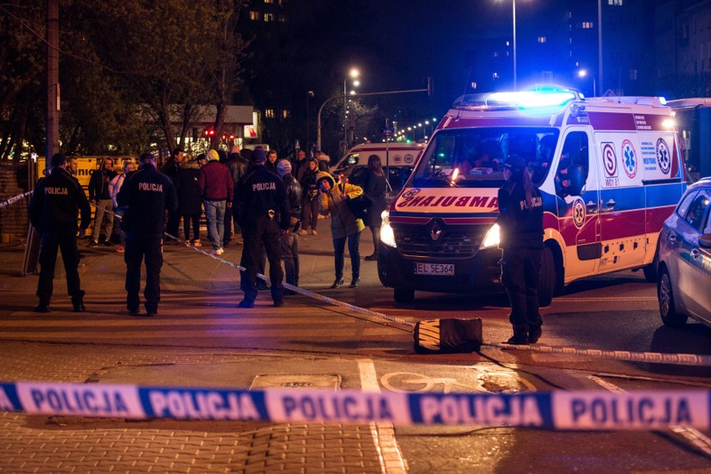 Police officers investigate the site of stabbing in Warsaw