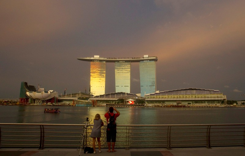FILE PHOTO: File picture shows tourists standing at a promenade across the water from the Marina Bay Sands integrated resort in Singapore