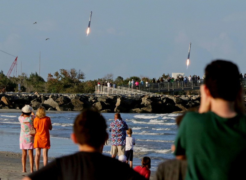 Spectators watch from Jetty Park as booster rocket engines approach landing pads after a SpaceX Falcon Heavy rocket lifted off from the Kennedy Space Center