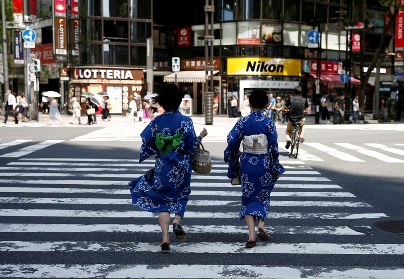 FILE PHOTO: Girls wearing the yukata, or casual summer kimono, run as they cross the road at a shopping district in Tokyo