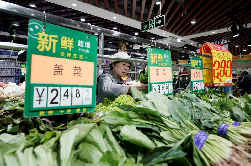 A woman selects vegetables at a supermarket in Beijing