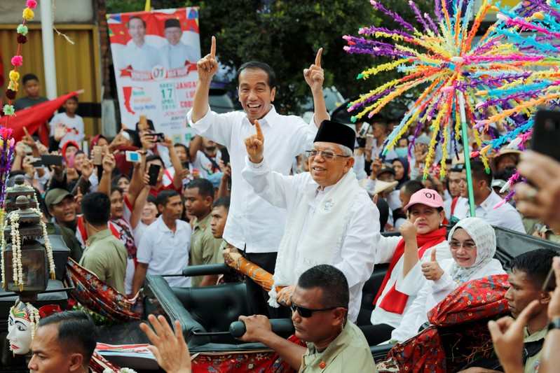 FILE PHOTO: Indonesia's President and presidential candidate for the next election Joko Widodo and his running mate for the upcoming election Ma'ruf Amin gesture as they greet their supporters at a carnival during campaign rally in Tangerang