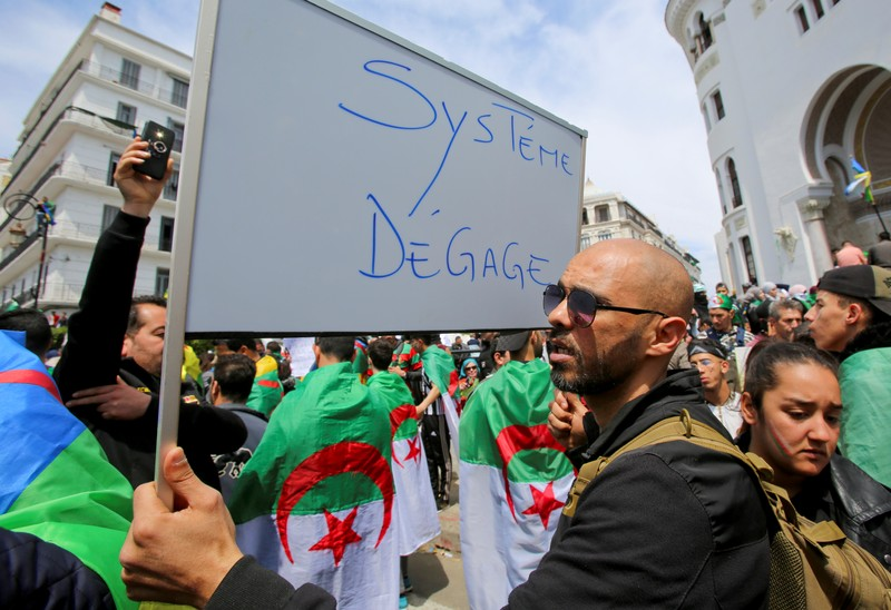 A man carries a sign during a protest seeking the departure of the ruling elite in Algiers