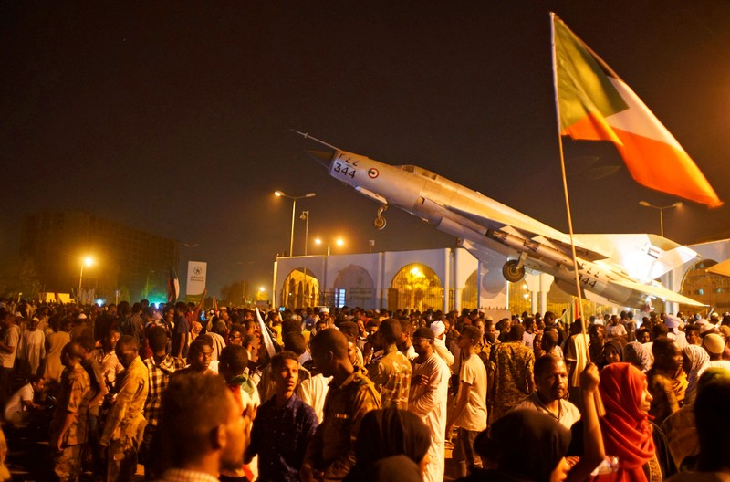Sudanese demonstrators celebrate after the Defence Minister Awad Ibn Auf stepped down as head of the country's transitional ruling military council, as protesters demanded quicker political change, outside the Defence Ministry in Khartoum