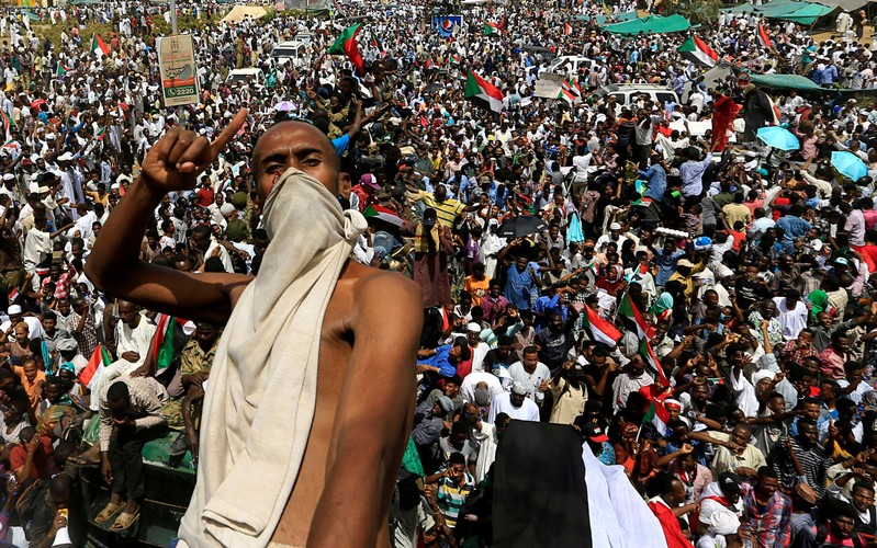 A Sudanese demonstrator gestures while riding atop a military truck as he protests against the army's announcement that President Omar al-Bashir would be replaced by a military-led transitional council, near Defence Ministry in Khartoum