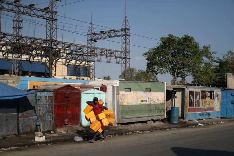 A man carries containers used to filled them with fuel that is sold on the black market in Port-au-Prince