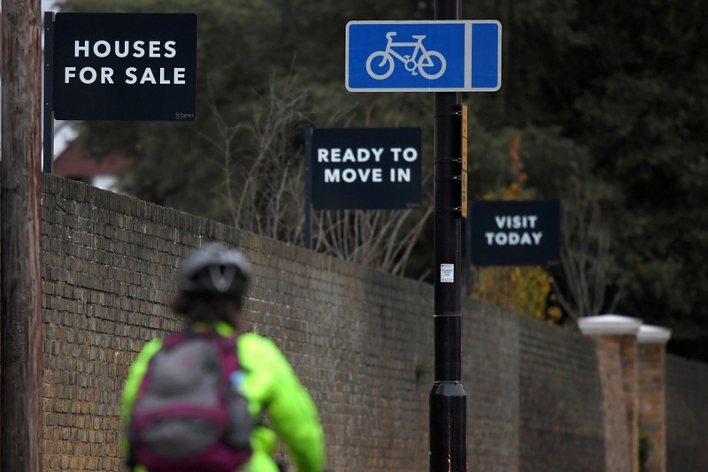 FILE PHOTO: Property sale signs are seen outside of a group of newly built houses in west London