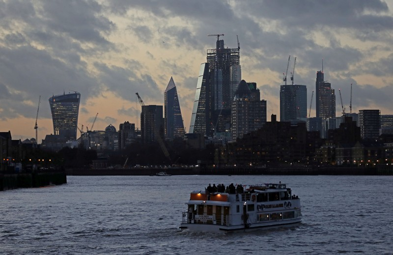 FILE PHOTO: A river boat cruises down the River Thames as the sun sets behind the Canary Wharf financial district of London