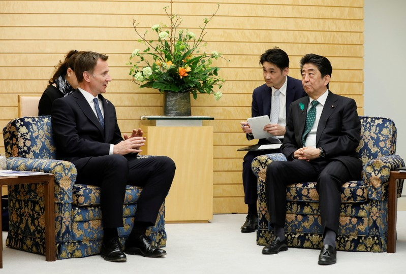 Jeremy Hunt, British Secretary of State for Foreign and Commonwealth Affairs, talks with Japanese Prime Minister Shinzo Abe