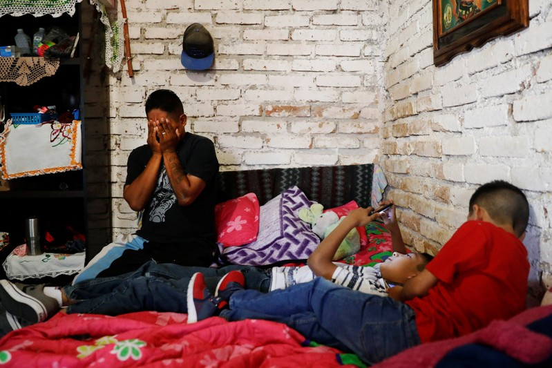 Arturo, a Mexican migrant, reacts next to his sons inside their house in Neutla