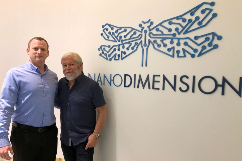 Israeli company Nano Dimension CEO Amit Dror and Chairman Avi Reichental, pose for a picture next to the company logo during an interview with Reuters in Ness Tziona, Israel