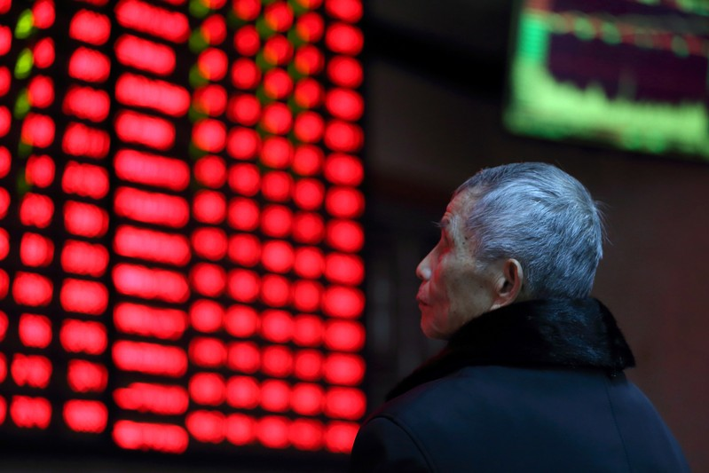 FILE PHOTO:  A man looks on in front of an electronic board showing stock information at a brokerage house in Nanjing