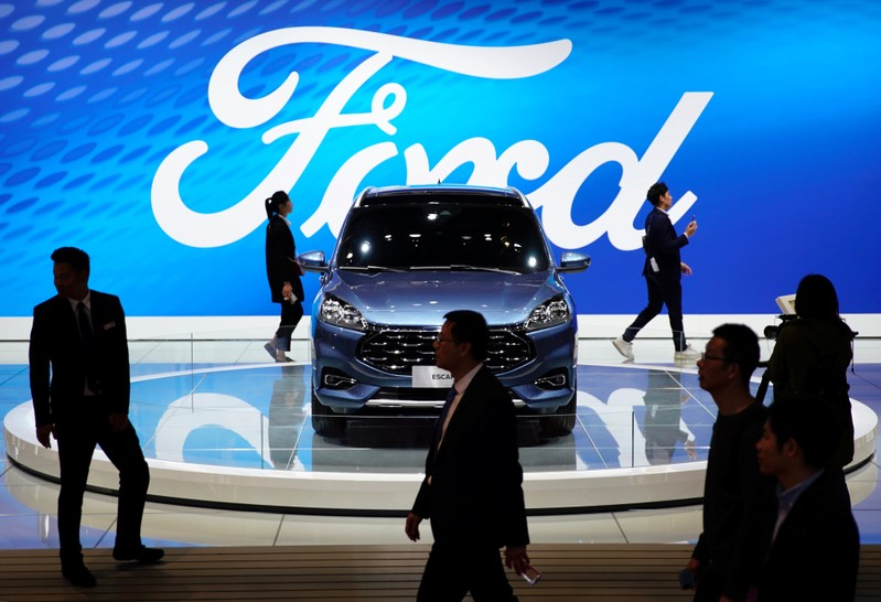 FILE PHOTO: People walk by a Ford Escape SUV displayed during the media day for the Shanghai auto show in Shanghai