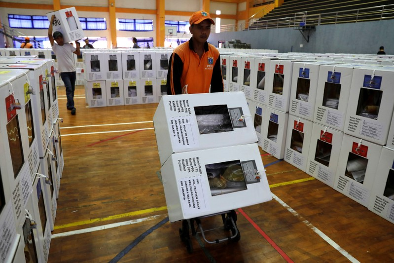 A worker carries election materials with a trolley to be distributed to polling stations from a warehouse in Jakarta