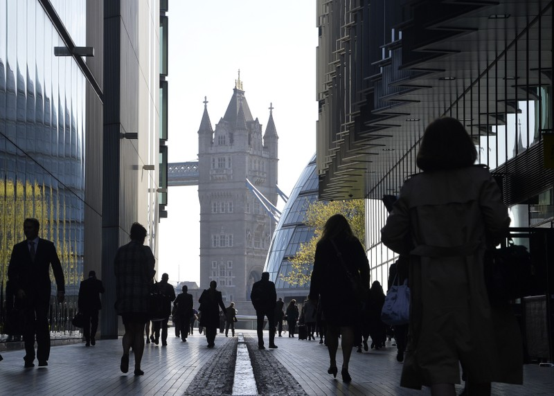 FILE PHOTO: City workers head to work during the morning rush hour in London