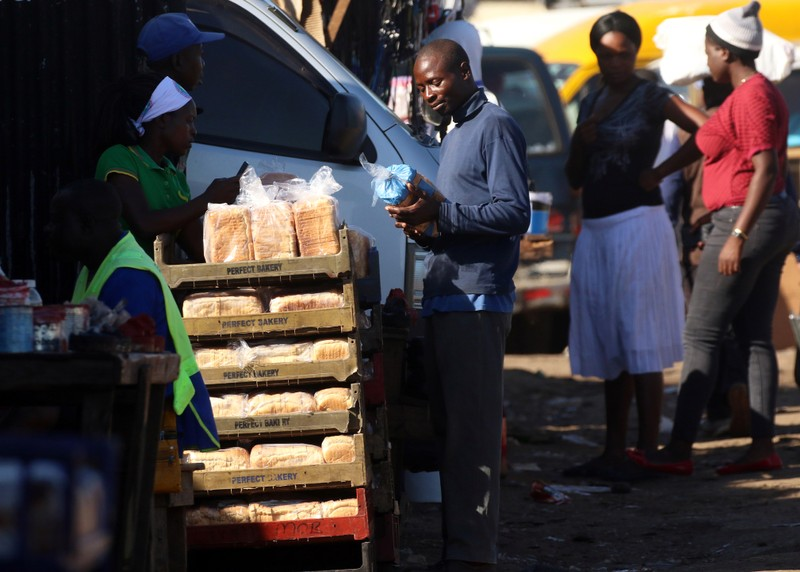 A man buys bread from a street vendor in Mbare township