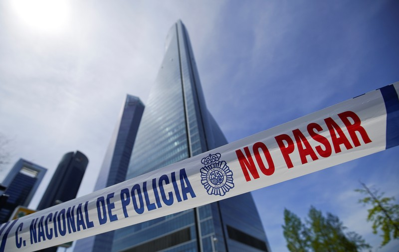 A police tape is pictured in front of the towers of a skyscraper housing embassies, after a bomb threat, in Madrid