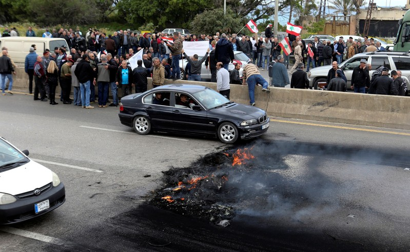 Retired army officers hold Lebanese flags as they block a highway during a protest in Naameh, south of Beirut