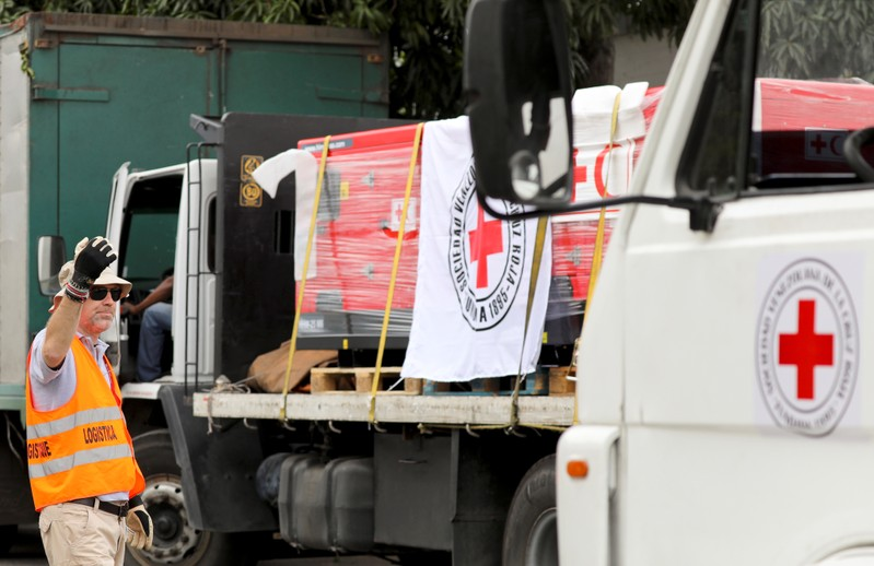 A worker directs trucks with logo of the International Federation of Red Cross and Red Crescent Societies (IFRC) carrying humanitarian aid, at a warehouse where the aid will be stored, in Caracas