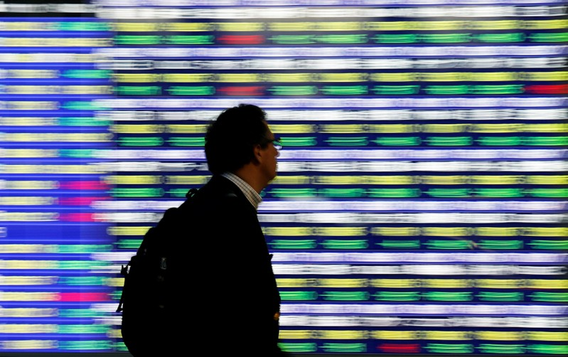 FILE PHOTO: A man walks past an electronic stock quotation board outside a brokerage in Tokyo