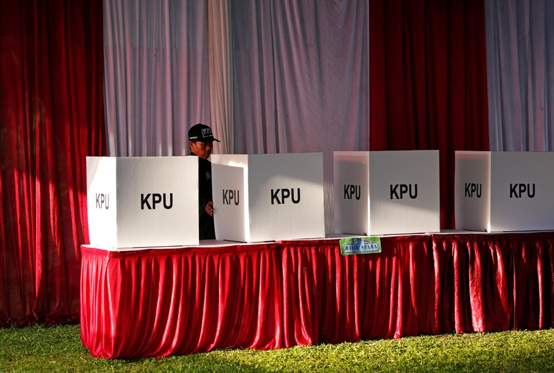A security personnel checks ballot boxes before polls open during elections in Bogor
