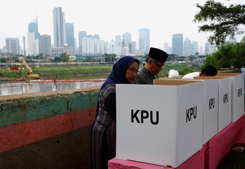 Voters mark their ballots at a polling centre during elections in Jakarta, Indonesia