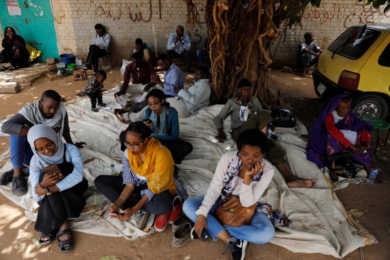 Sudanese demonstrators rest under the shadow of a tree in front of the Defence Ministry in Khartoum