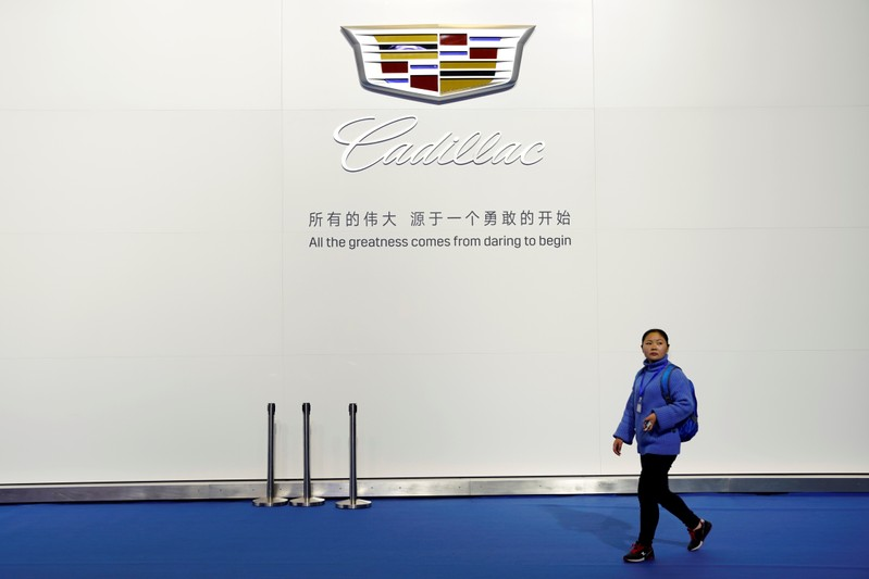 Woman walks past a board with a sign of Cadillac of GM during the media day for Shanghai auto show