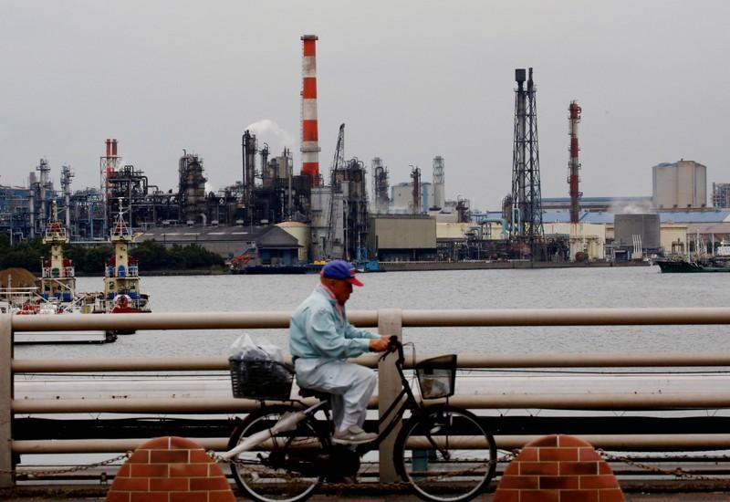 FILE PHOTO: A man cycles past chimneys of facotries at the Keihin Industrial Zone in Kawasaki