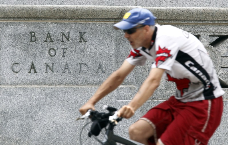 A cyclist rides past the Bank of Canada building in Ottawa