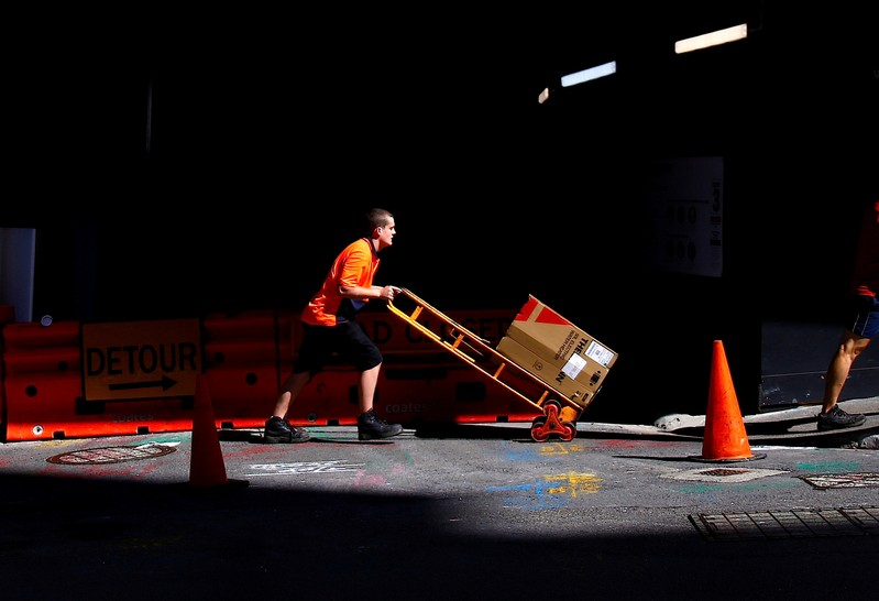 FILE PHOTO: A worker pushes a trolley loaded with goods past a construction site in the central business district of Sydney