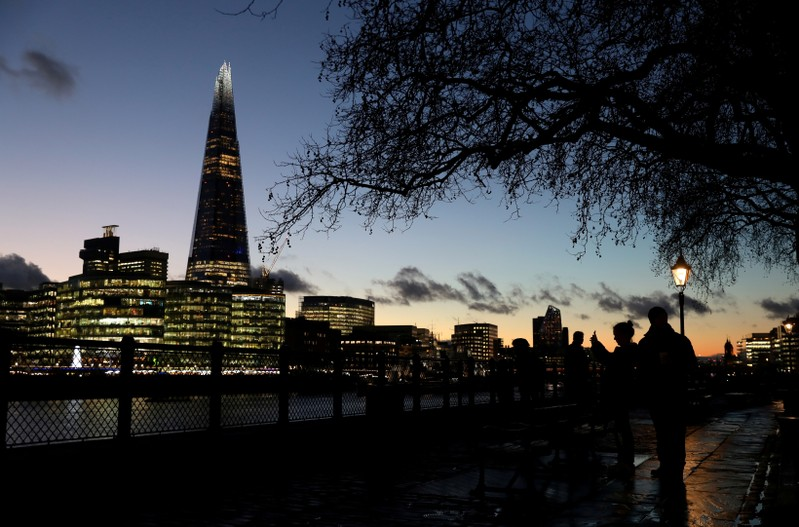 FILE PHOTO: People walk alongside the Thames as the sun sets behind The Shard in London