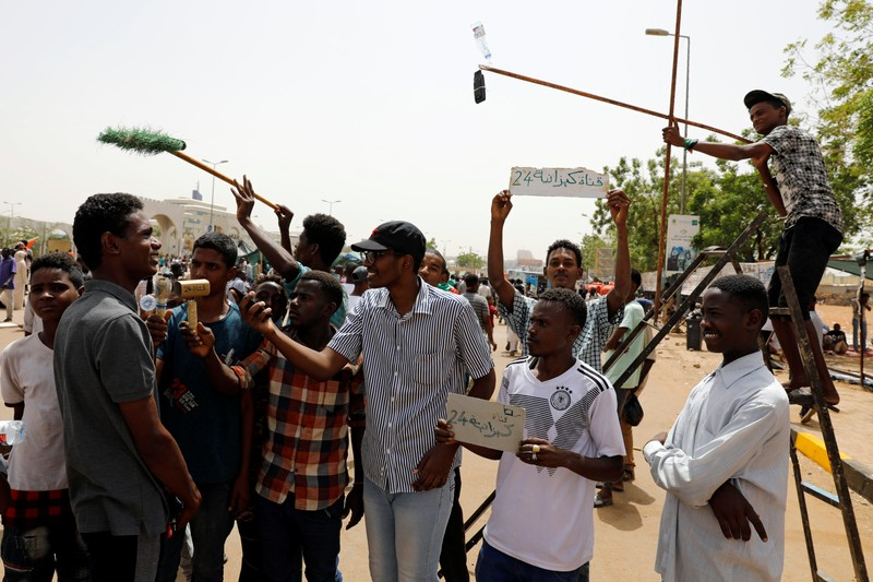 A group of protesters acting like a mock TV crew interview a demonstrator in front of the Defence Ministry in Khartoum