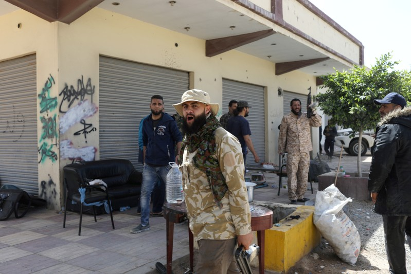 Members of Libyan internationally recognised government forces react during the fighting with Eastern forces at Al-Swani area in Tripoli