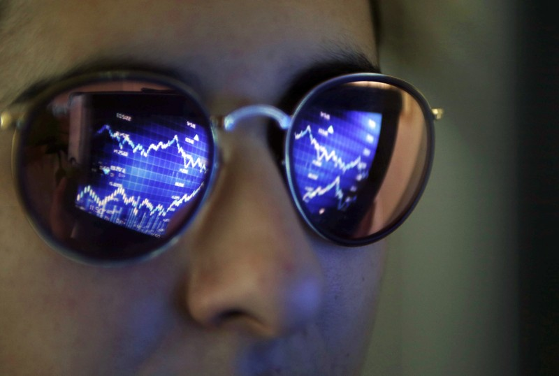 A computer screen showing stock graphs is reflected on glasses in this illustration photo taken in Bordeaux