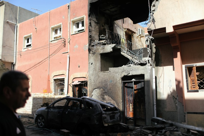 A Libyan man walks near a house damaged by an overnight shelling in Abu Salim district in Tripoli