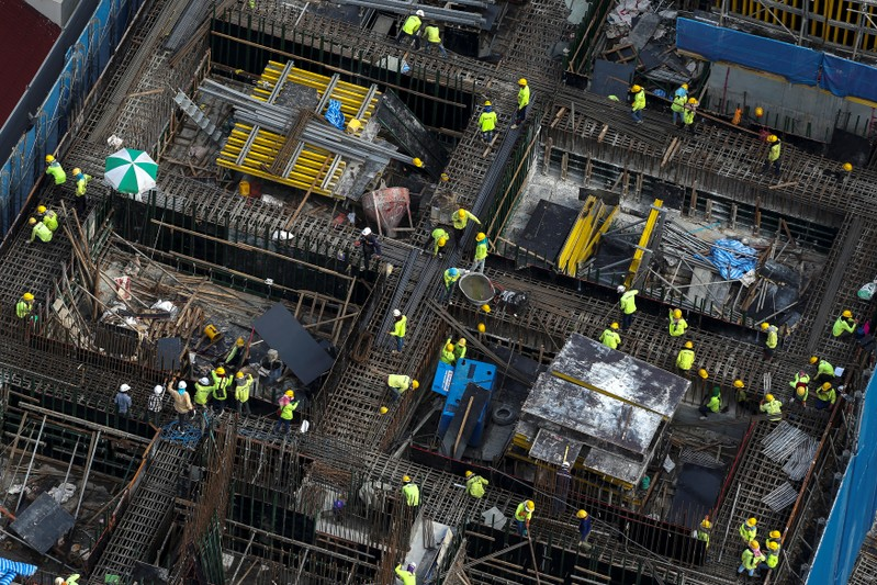FILE PHOTO: Workers work at a construction site in central Bangkok