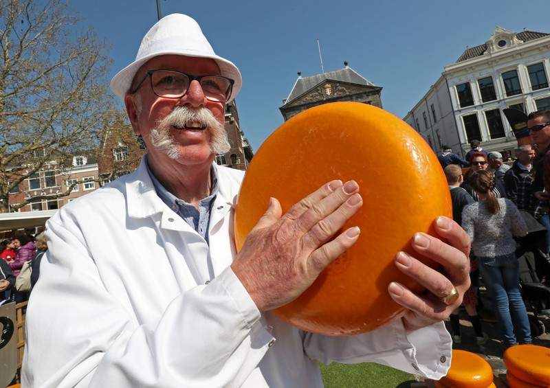 A seller holds a piece of Gouda cheese at the cheese market in Gouda