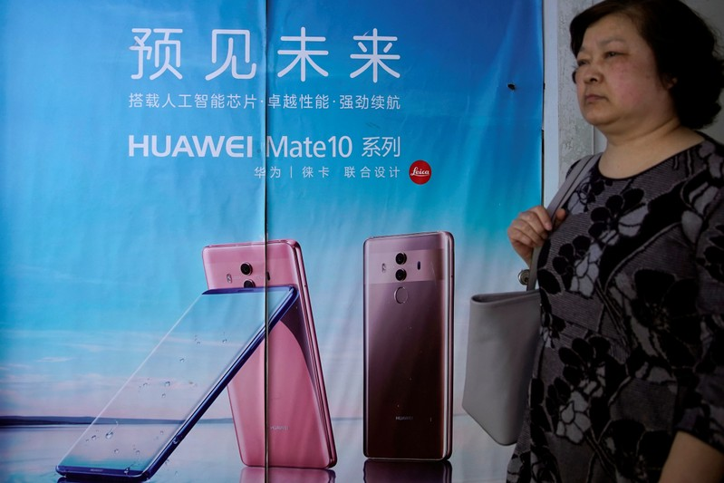 Woman walks past an advertisement on an elevator showing Huawei P30 series phones with a camera system co-developed with Leica, in Shanghai
