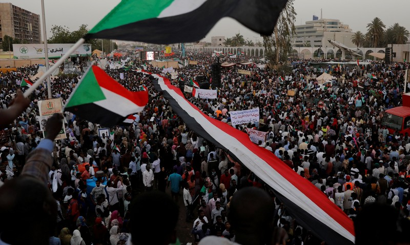 FILE PHOTO: Thousands of protesters wave Sudanese flags, hold banners and chant slogans during a demonstration in front of the Defence Ministry in Khartoum