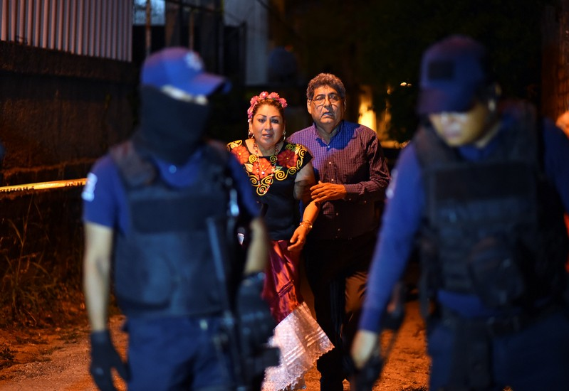 People react next to police officers guarding a crime scene where unidentified assailants opened fire at a bar in Minatitlan