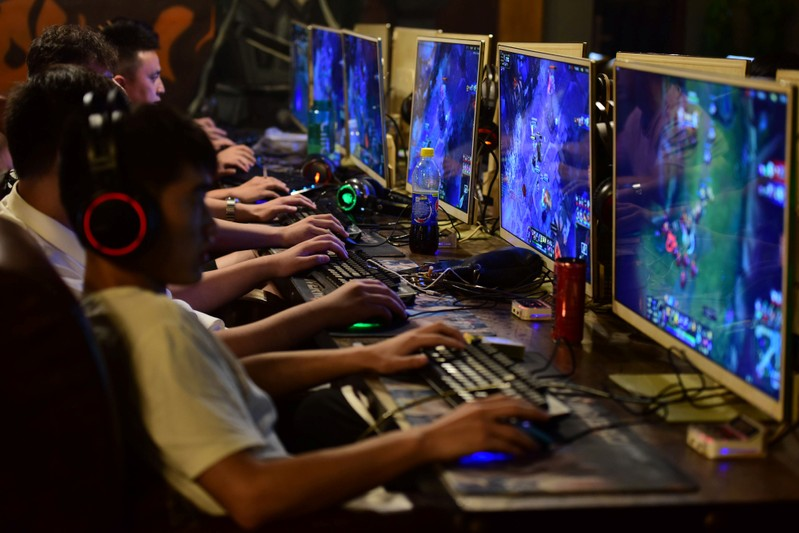 People play online games at an internet cafe in Fuyang