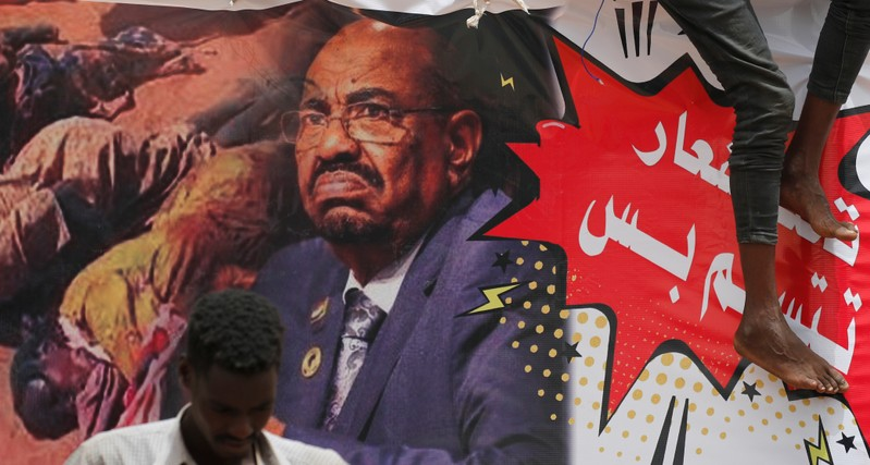 FILE PHOTO - A protester stands in front of a banner depicting former Sudanese President Omar al-Bashir in front of the Defence Ministry in Khartoum