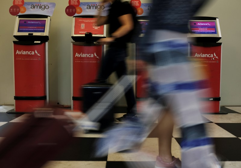 Customers walk past Avianca airline check-in machines at Congonhas airport in Sao Paulo