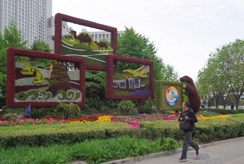 Man walks past a flower installation set up for the upcoming Belt and Road Forum in front of the Chinese Foreign Ministry in Beijing