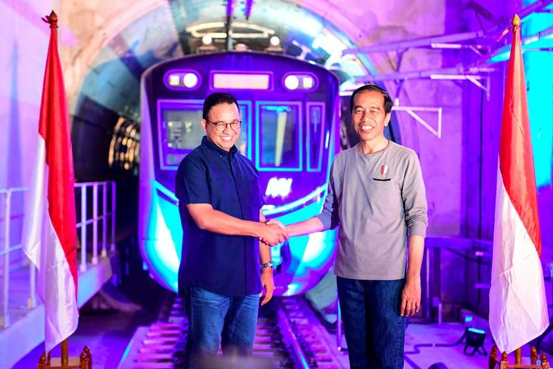 FILE PHOTO - Indonesia's President Joko Widodo (R) shakes hands with Governor of Jakarta Anies Baswedan (L) during Jakarta Mass Rapid Transit (MRT) first-phase launching at Bundaran HI station in Jakarta